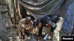 Жарылыс болған жерді зерттеп жатқан пәкістандық полиция өкілдері. 10 мамыр 2011 жыл. Көрнекі сурет.