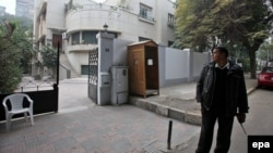 Жөнөкөй кийимчен полициячы бейөкмөттүк уюмдун кеңсесин күзөтүүдө. Каир. 30-декабрь 2011