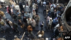 Pakistanis gather among the wreckage a day after two powerful bomb blasts at a market in Lahore.