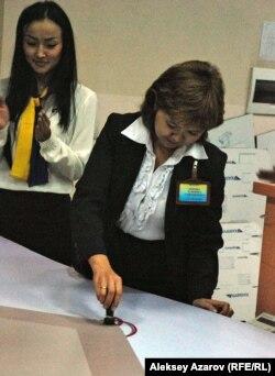 Сотрудница почты наносит оттиск штемпелем на гигантский конверт с поздравлениями Назарбаеву. Алматы, 29 ноября 2012 года.