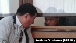 Адвокат Ермек Сыздықов (сол жақта) айыпталушы Руслан Темірболатовпен сот залында сөйлесіп отыр. Астана, 13 маусым 2014 жыл.