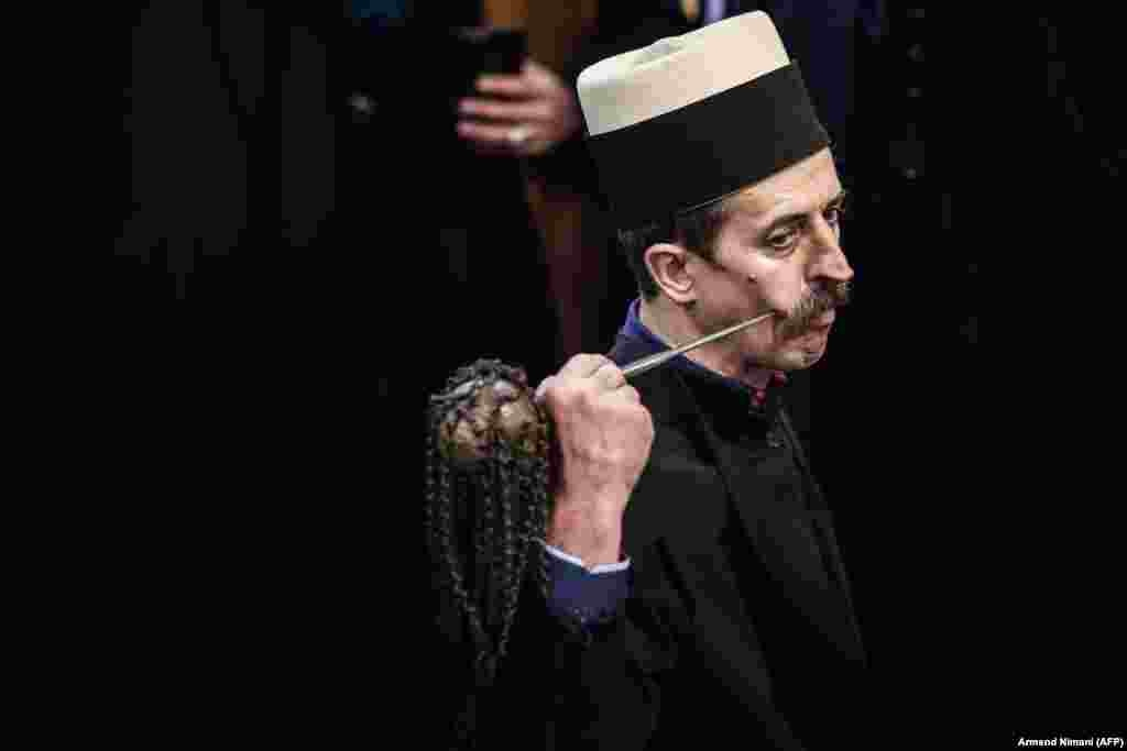 A Kosovar dervish pierces his cheek with a needle during a ceremony in Prizren during Persian New Year celebrations. The Kosovar dervish community carries on centuries-old mystical practices, such as self-piercing with needles and knives as a way to earn salvation and find the path to God. (AFP/Armend Nimani)