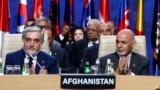 FILE: Afghan President Ashraf Ghani (R) and Afghanistan's Chief Executive Abdullah Abdullah applaud during a session at the NATO Summit in Warsaw in July 2016.