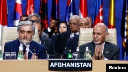 Afghanistan's President Ashraf Ghani (R) and Afghanistan's Chief Executive Abdullah Abdullah applaud during a session at the NATO Summit in Warsaw, Poland on July 9.