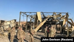 U.S. soldiers inspect the site where an Iranian missile hit at Ain al-Asad air base in Anbar province, January 13, 2020