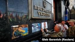 Участники акции «Нет капитуляции» обклеивают стены здания Офиса президента Украины фотографиями погибших участников боевых действий на Донбассе. Киев, 14 октября 2019 года