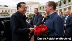 Russian Prime Minister Dmitry Medvedev (right)welcomes Chinese Premier Li Keqiang in St. Petersburg on September 16.