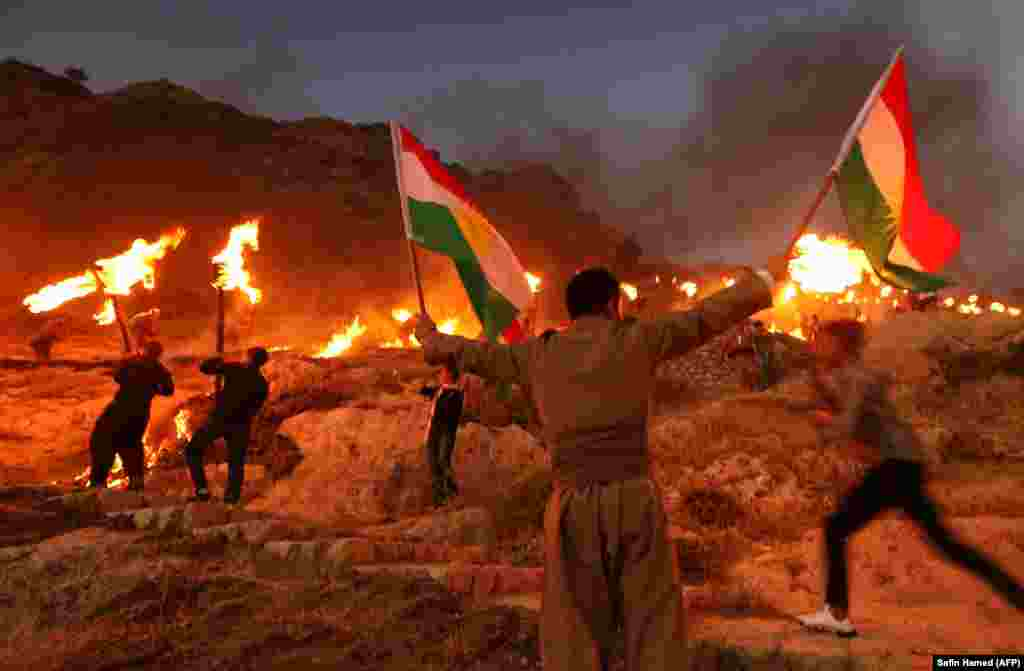 Iraqi Kurds wave Kurdish flags and hold burning torches as they walk up a mountain during a gathering to show support for the upcoming independence referendum and encourage people to vote in the town of Akra, some 500 kilometers north of Baghdad. (AFP/Safin Hamed)
