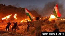 Iraqi Kurds wave Kurdish flags and hold burning torches as they walk up a mountain during a gathering to show support for the upcoming independence referendum and encourage people to vote in the town of Akra, some 500 kilometres north of Baghdad,