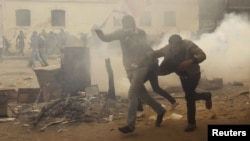 Демонстранты бегут во время столкновений с полицией. Каир, 3 февраля 2012 года.