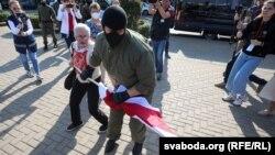 Сотрудник ОМОНа отбирает флаг у пенсионерки Нины Багинской