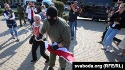 Сотрудник ОМОНа отбирает флаг у пенсионерки Нины Багинской, 26 сентября 2020 г.