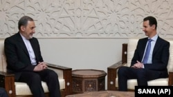 Syrian President Bashar Assad (R) meets with Akbar Velayati, a top adviser to Iran's supreme leader, in Damascus, April 12, 2018