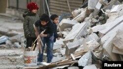 Սիրիա - Հալեպի թաղամասերից մեկում երեխաները վառելափայտ են հավաքում ռմբակոծության հետևանքով ավերված շենքի փլատակներից, նոյեմբեր, 2016թ․