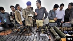 Security officials in Pakistan display arms and ammunition seized after a terrorists attack on the Sri Lankan cricket team in Lahore.