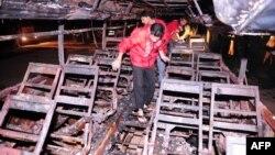 Рятувальники шукають останки тіл у згорілому автобусі біля Карачі, 11 січня 2015 року