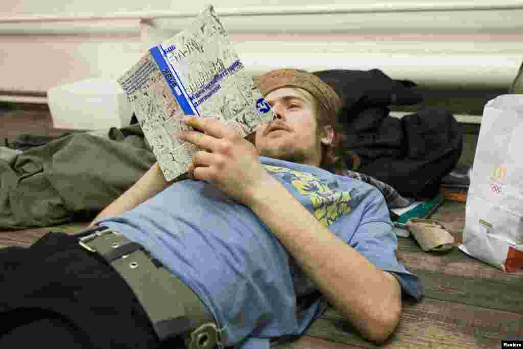 Political activist Pyotr Verzilov, the husband of Pussy Riot member Nadezhda Tolokonnikova, reads a book about anarchism by U.S. author Bob Black in Moscow in January 2009.