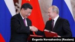 Қытай лидері Си Цзиньпин (сол жақта) мен Ресей президенті Владимир Путин келісімге қол қойғаннан кейін. Мәскеу, 5 маусым 2019 жыл.