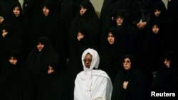 FILE PHOTO: A woman from an African Islamic country (in white) stands among Iranian women during the national anthem of Iran at the opening session of the 8th Islamic Conference Summit in Tehran's new conference building on December 9. REUTERS/Yannis Behr