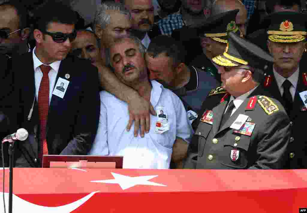 The father of late Turkish soldier Hamza Yildirim (second left) reacts in front of his son's flag-draped coffin during his funeral ceremony at Kocatepe Mosque in Ankara, Turkey, on July 31. Yildirim died when Kurdish militants attacked his convoy in the southeastern province of Sirnak. (AFP/Adem Altan)