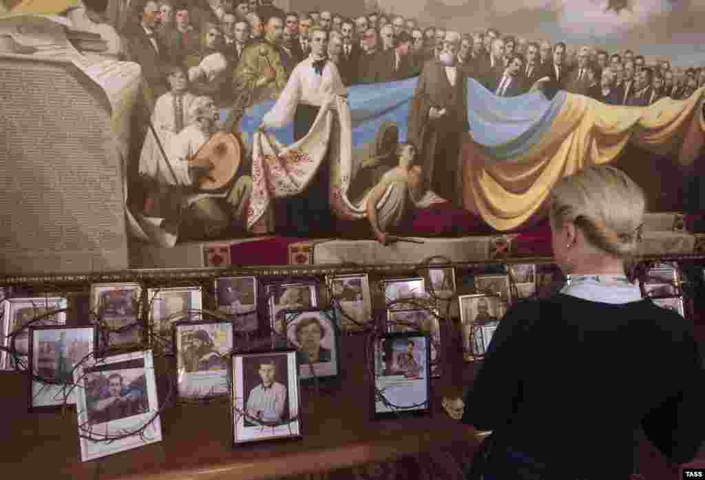 A woman looks at portraits of those who were killed during the recent unrest in Kyiv, which are dispalyed in a parliament corridor. (ITAR-TASS/Maksim Nikitin)