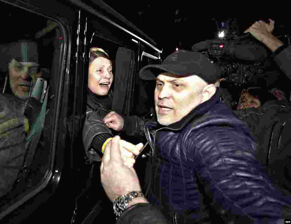 Харьковның Үзәк клиник хастаханәсеннән чыккан Тимошенко машинадан үз тарафдарларын сәламли.