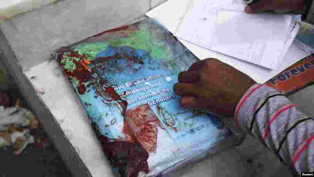 A rescue worker inspects blood-stained paperwork that was being carried by Nasima Bibi, who was shot and killed by gunmen in Karachi on December 18. (Reuters/Athar Hussain)