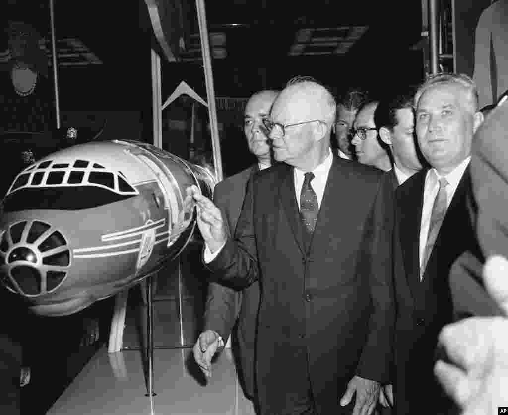 U.S. President Dwight D. Eisenhower inspects a model of the TU-114 aircraft that had transported a Soviet delegation from Moscow for the event.