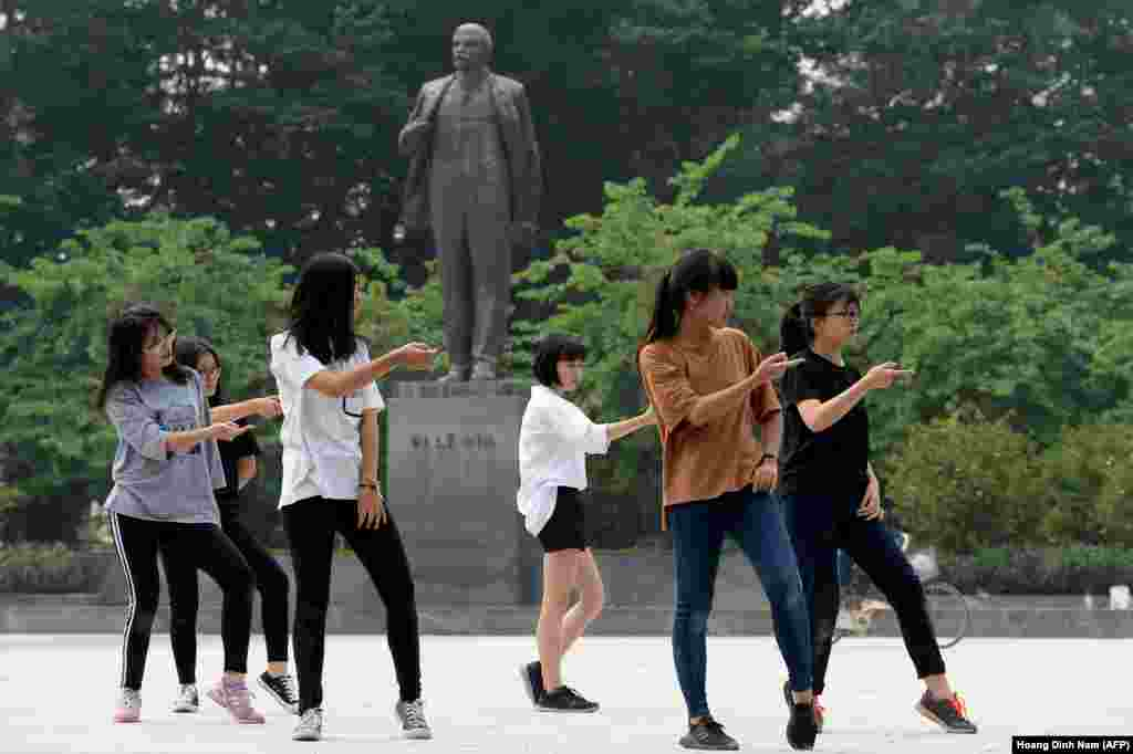 Hanoi, Vietnam: Lenin looking a little clay-footed behind the nimble-stepping youngsters practicing dance routines on Lenin square.