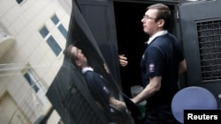 Former Ukrainian Interior Minister Yuriy Lutsenko gets into a police truck after a court session in Kyiv in August 2012.