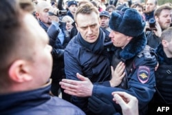 Police officers detain Kremlin critic Aleksei Navalny (center) during an anticorruption rally in central Moscow on March 26.