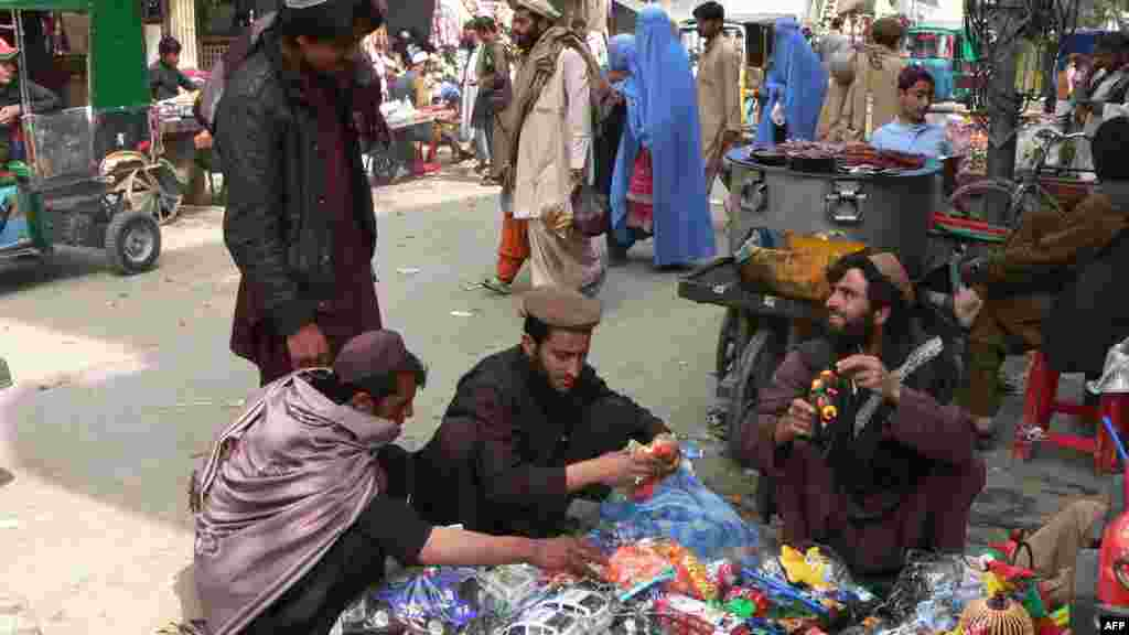 Afghanistan -- Men and women prepare to celebrate the traditional new year by purchasing gifts in Jalalabad, 19Mar2012