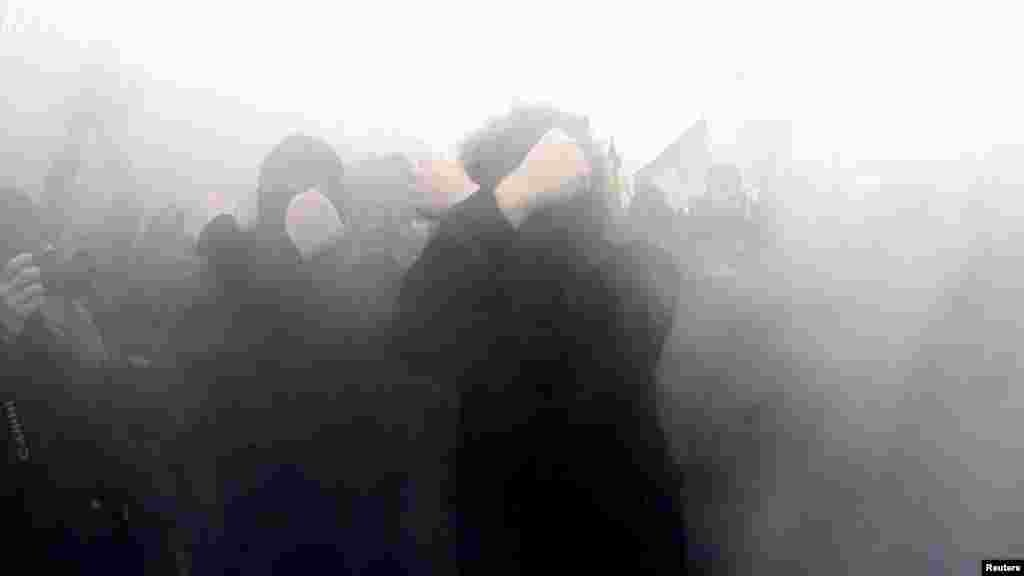 Nationalists cover their faces as they walk through smoke during the march.