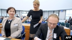 Yulia Tymoshenko's daughter Yevhenia Tymoshenko talks with her mother's lawyers Serhiy Vlasenko (right) and Valentyna Telychenko at the European Court of Human Rights in Strasbourg on August 28.