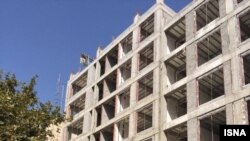 Apartment building under construction in Tehran on land granted for religious purposes.