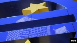 The building of the European Central Bank (ECB) reflected in the Euro sign logo by artist Otmar Hoerl in Frankfurt am Main.