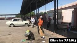 Дворник убирает мусор на территории автовокзала.