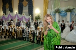 Гульнара Каримова, дочь президента Узбекистана, выступает на благотворительной акции «Тысяча свадеб» в 2012 году.