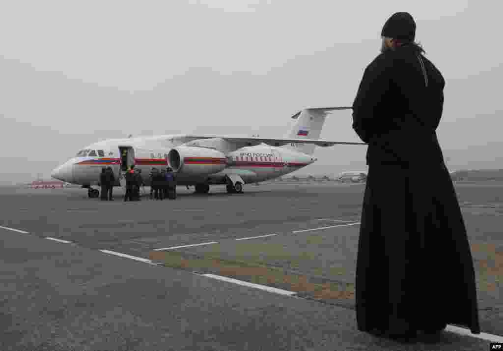 An Orthodox priest in St. Petersburg looks on as employees from the Russian Ministry for Emergency Situations prepare to unload the bodies of people who died in an Egyptian plane late last month. (AFP/Dimitry Lovetsky)
