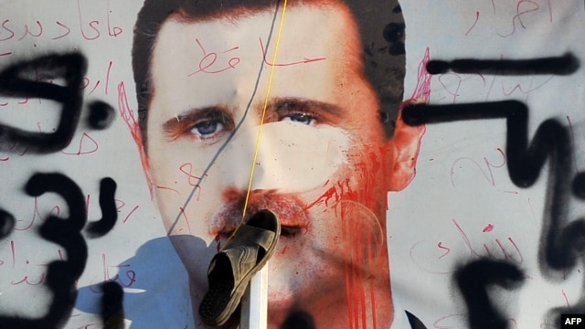 A vandalized poster of Syrian President Bashar al-Assad in a trash container in the northern city of Aleppo.