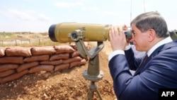 Arxiv fotosu: Türkiyənin Baş naziri Ahmet Davudoğlu Suriya ərazisində baxır.