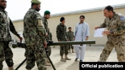 Afghanistan - An Armenian military instructor (R) trains Afghan soldiers.