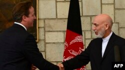 Afghan President Hamid Karzai (right) shakes hands with British Prime Minister David Cameron during a press conference at the presidential palace in Kabul on June 29.
