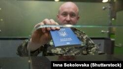 Пограничник показывает украинский загранпаспорт нового образца. Введение биометрических паспортов усложнило крымчанам поездки за рубеж. Ранее для получения загранпаспорта не требовалось личное присутствие