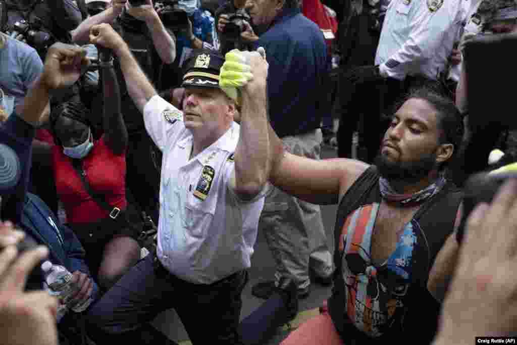 Њујорк - Началникот на Одделот за полиција во Њујорк, Теренс Монахан, клечи на колено со активисти, додека демонстрантите шетаа во градот, понеделник, 1 јуни 2020 година. Демонстрантите излегоа на улиците на Њујорк во знак на протест против смртта на Џорџ Флојд, кој почина на 25 мај, откако беше притиснат на вратот од полицискиот службеник во Минеаполис.