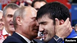 Russian President Vladimir Putin (left) congratulates Russia's Tagir Khaibulayev after he defeated Mongolia's Tuvshinbayar Naidan in their men's 100-kilogram final judo match at the London 2012 Olympic Games.