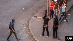رجل ملثّم من مجموعة من المحتجين ضد حكم الجيش في مصر يصوب مسدسه في إشتباكات مع قوات الأمن بالقاهرة