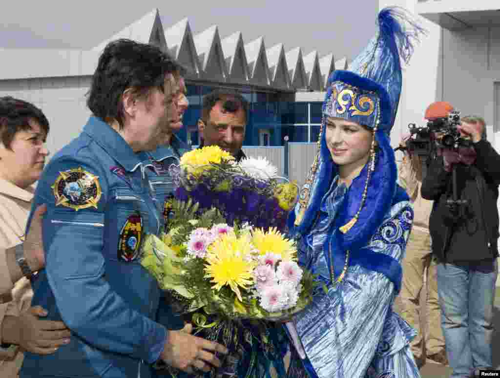 Revin is welcomed on his arrival to the city of Qostanai, the site of a forward base in northern Kazakhstan where the three were taken by helicopter.