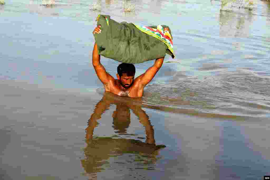 A Pakistani carrying his possessions wades through floodwater in the area of Larkana. According to Pakistani officials, the death toll from three weeks of floods has reached 118. (epa/Waqar Hussein)
