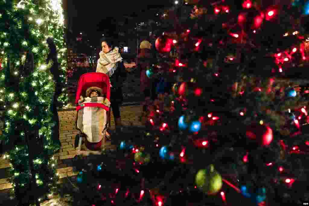Жінка з дитиною в дитячій колясці стоїть у парку, прикрашеному на Різдво в Києві